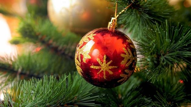 Фото крупного плана красного сверкающего шара на красивой рождественской елке. идеальный абстрактный фон для зимних праздников или торжеств