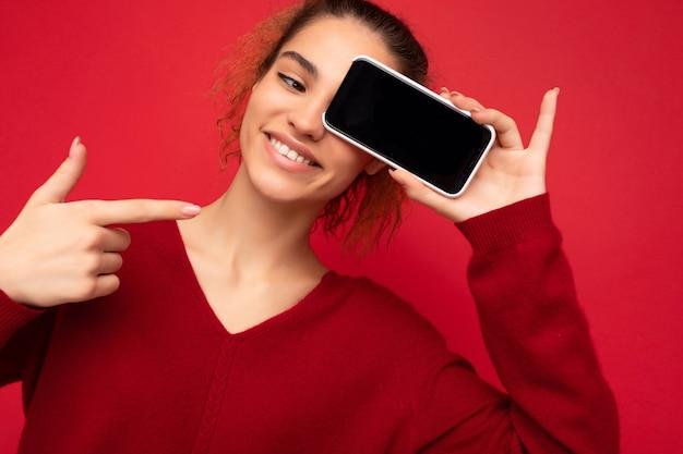 赤の上に分離された濃い赤のセーターを着て幸せな面白い若い女性の笑顔のクローズアップ写真