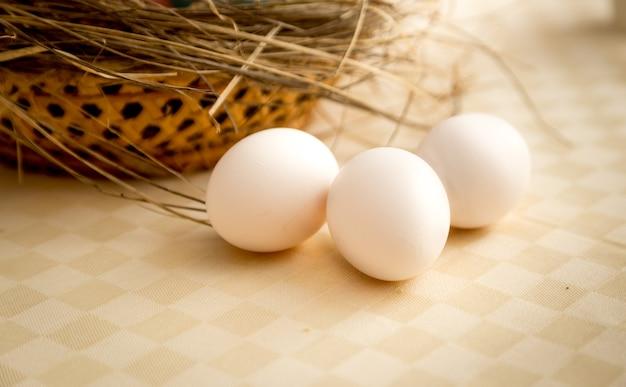 Крупным планом фото трех белых яиц, лежащих на столе рядом с корзиной