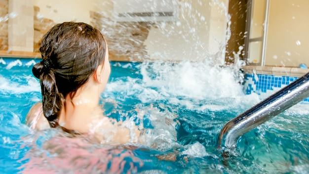 수영장에서 놀고 물을 튀기는 두 십대 소녀의 근접 촬영 사진