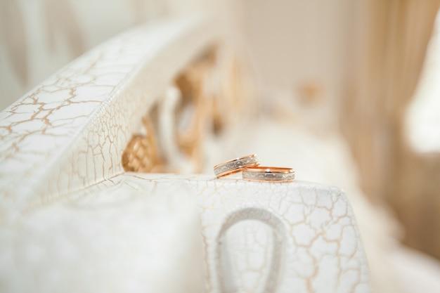 Крупным планом фото двух обручальных золотых колец.