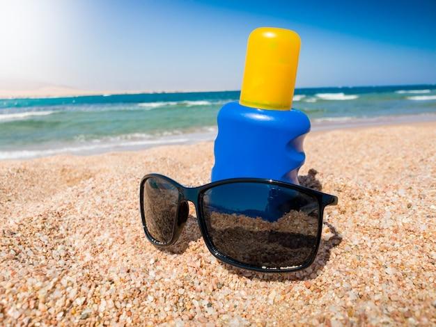 海の砂浜に横たわっている青いボトルとサングラスのuv日焼け止めローションのクローズアップ写真。夏休みのイラストにぴったりの画像です。