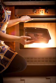 오븐에서 초콜릿 쿠키를 요리하는 여자의 근접 촬영 사진