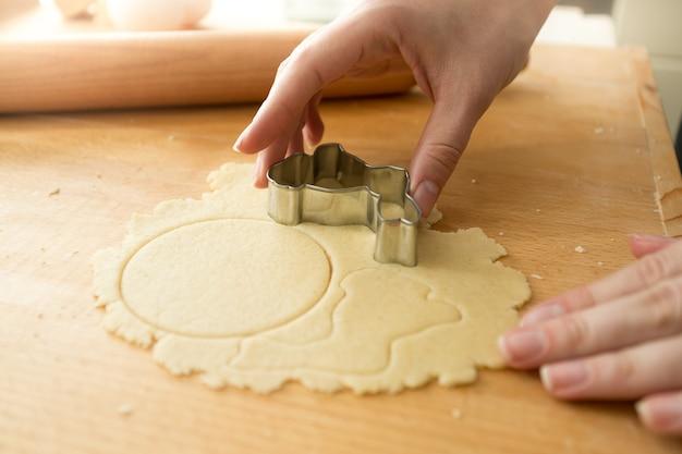 Крупным планом фото женщины, резающей тесто с металлической формой