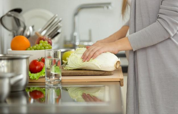 スープ用の新鮮なキャベツを切る女性のクローズアップ写真