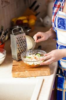 キッチンでフォークとサラダを食べる女性のクローズアップ写真