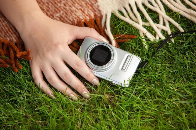 Крупным планом фото женщины, держащей компактный фотоаппарат на траве