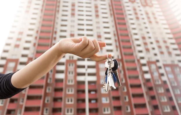 Крупным планом фото женщины, держащей ключи от новой квартиры