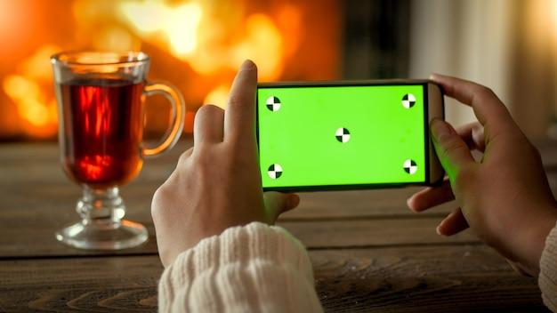 Крупным планом фото женщины, держащей мобильный телефон с зеленым ключевым экраном chroma в комнате, оформленной на рождество. идеальный образ для праздничной рекламы. разместите собственное изображение