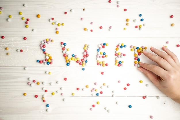 Крупным планом фото женщины, делая слово сладкое из красочных конфет