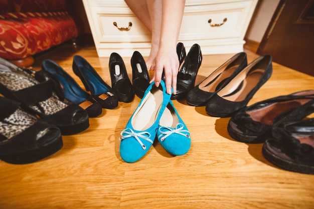 Крупным планом фото женщины, выбирающей балетки, а не высокие каблуки