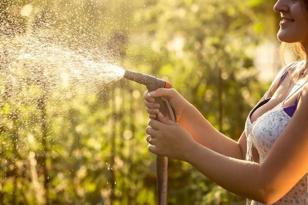 暑い晴れた日にホースパイプで庭に水をまく女性のクローズ アップ写真