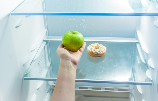 Крупным планом фото женщины, держащей яблоко вместо пончика в холодильнике