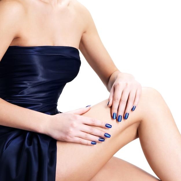 白で隔離の青い爪を持つ女性の手のクローズアップ写真