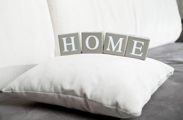 Крупным планом фото слова home по буквам на деревянных блоках, лежащих на диване
