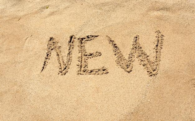 砂浜に書かれた新しい単語のクローズ アップ写真