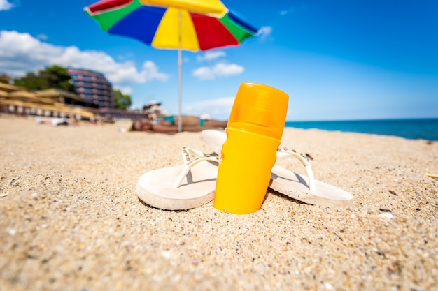 노란색 선탠 로션과 모래 해변에 누워 플립 플롭의 근접 촬영 사진