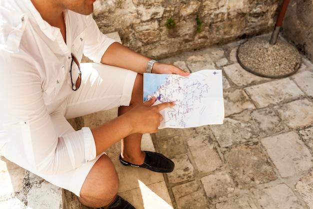 通りに座って、地図を指している若い男のクローズ アップ写真