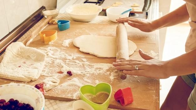 피자 반죽을 만드는 젊은 여자의 근접 촬영 사진