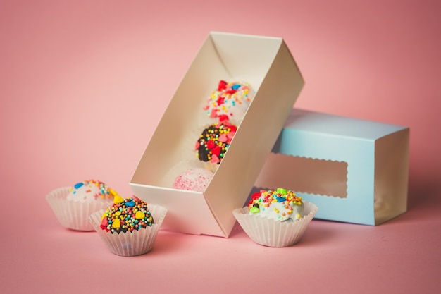 Closeup photo of open box with homemade cake balls with colorful sprinkles over pink surface