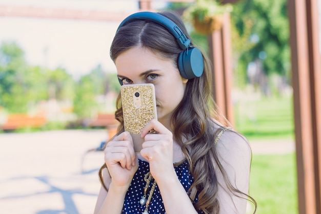 Closeup photo portrait of pretty attractive sweet lovely with coquettish looking at you eyes hiding face behind golden telephone case