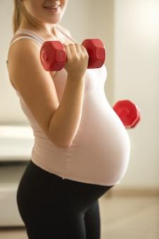 Closeup photo of pregnant woman lifting dumbbells