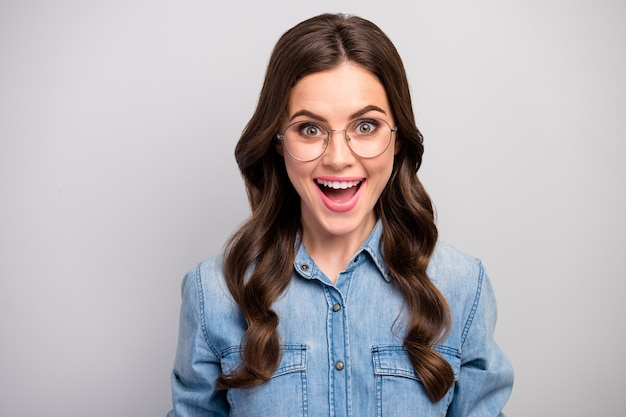 Closeup photo of pretty excited business lady open mouth listen positive good mood long curly hairdo wear specs casual jeans shirt isolated grey color