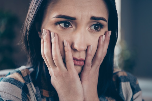Closeup photo of pretty lady holding hands on cheeks very sad expression did big life mistake wish turn time back sitting sofa wearing casual clothes apartment indoors