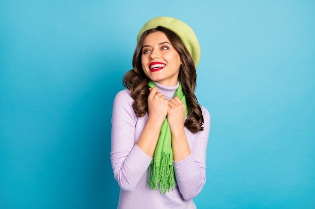 Closeup photo of pretty lady red lips toothy smiling good mood flirty look empty space wear green beret hat purple turtleneck scarf isolated blue color wall
