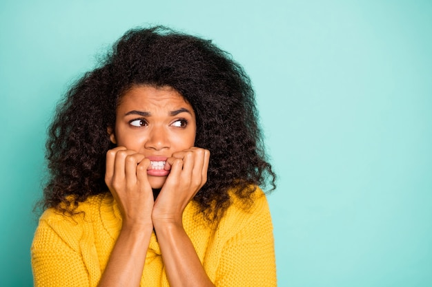 Closeup photo of pretty nervous dark skin lady holding fingers in mouth looking empty space wear yellow knitted jumper isolated blue teal color wall