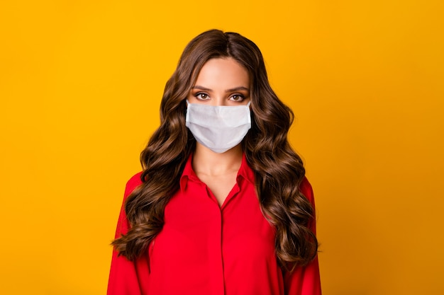 Closeup photo of pretty stunning curly business lady  serious bossy person wear medical mask office luxury red shirt isolated yellow vivid color background