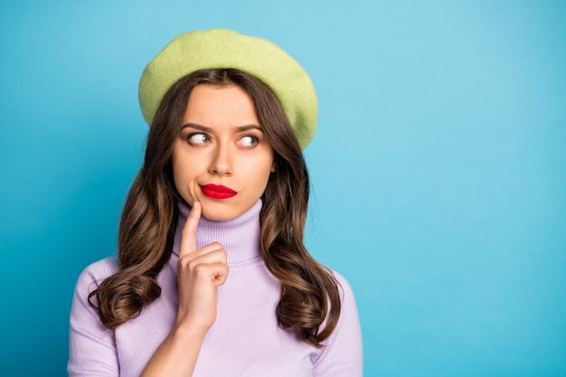 Closeup photo of pretty traveler lady look side empty space finger on chin have doubts making decision wear green beret hat purple turtleneck isolated blue color wall