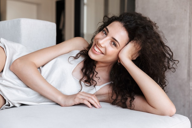 Closeup photo of pretty young woman with long curly hair wearing silk leisure clothing lying in hotel bed or sofa, and smiling while propping up her head with hand