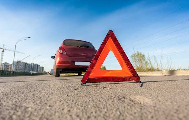 Closeup photo of red triangle sign on road next to broken car