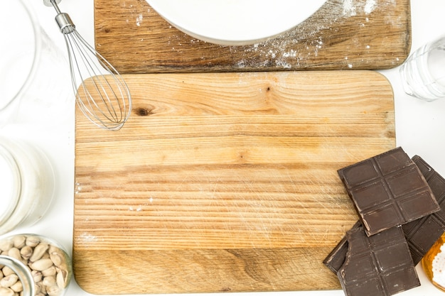 Closeup photo of rolling pin, chocolate, flour and dough lying on wooden board at kitchen
