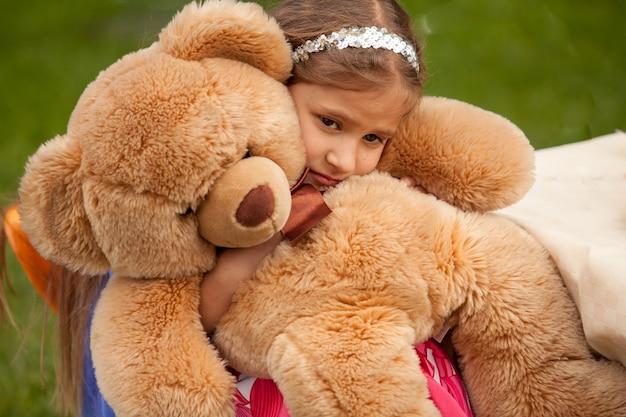 Closeup photo of sad little girl hugging teddy bear