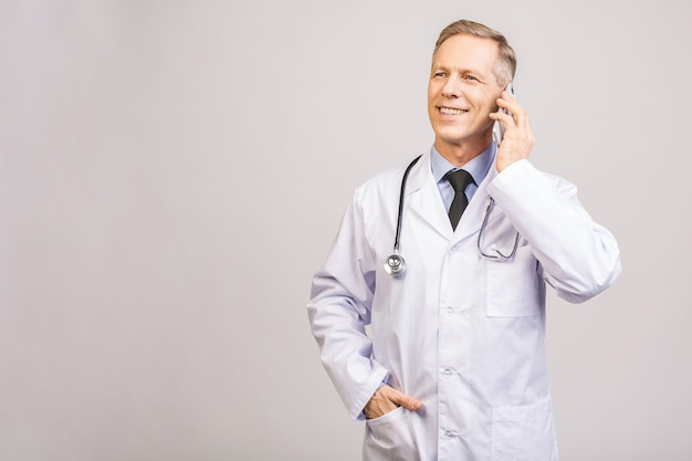 Closeup photo of senior man doctor standing isolated on grey background, using mobile phone.