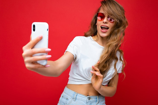 Closeup photo of sexy adult blonde female person holding mobile phone taking selfie photo using