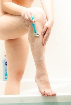 Closeup photo of sexy slim woman shaving legs at bathroom