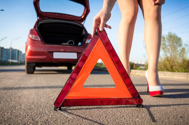 Closeup photo of sexy woman putting warning sign on road