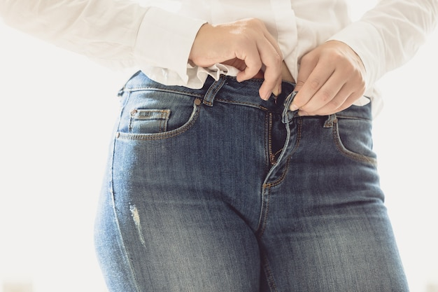 Closeup photo of sexy woman unbuttoning her jeans