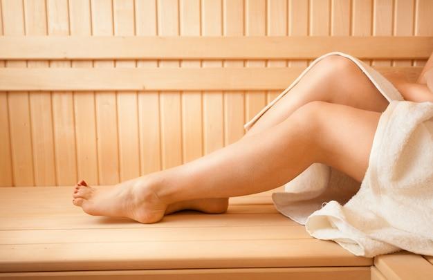 Closeup photo of sexy women feet on bench at sauna