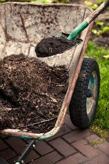 Closeup photo of spade putting soil in old wheelbarrow