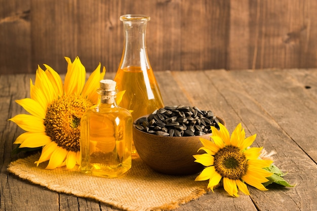 Closeup photo of sunflower oil with seeds on wooden table. bio and organic product concept.