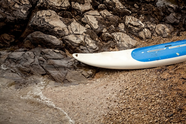 Closeup photo of surfboard lying on sandy beach at sea next to jagged cliffs