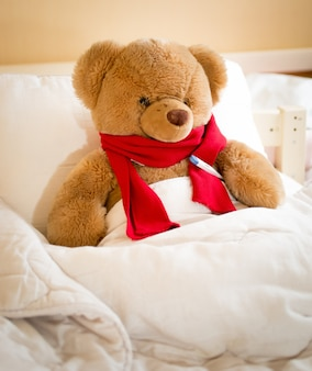 Closeup photo of teddy bear in red scarf lying in bed