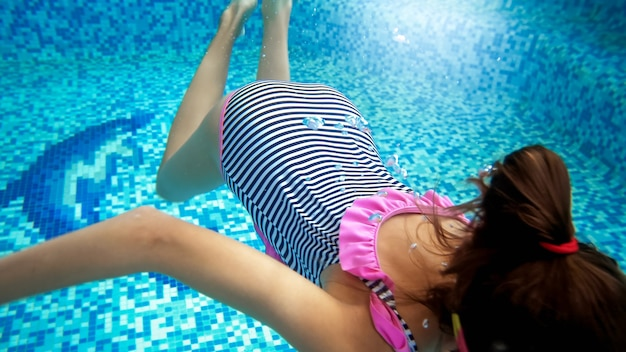 Closeup photo of teenage girl in goggles and striped swimsuit swimming underwater at swimming pool