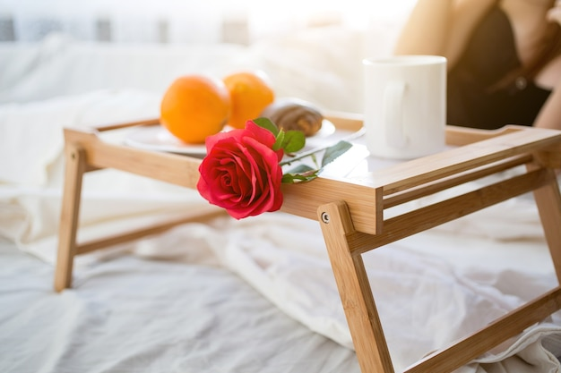 Closeup photo of tray with breakfast and red rose on bed at hotel room