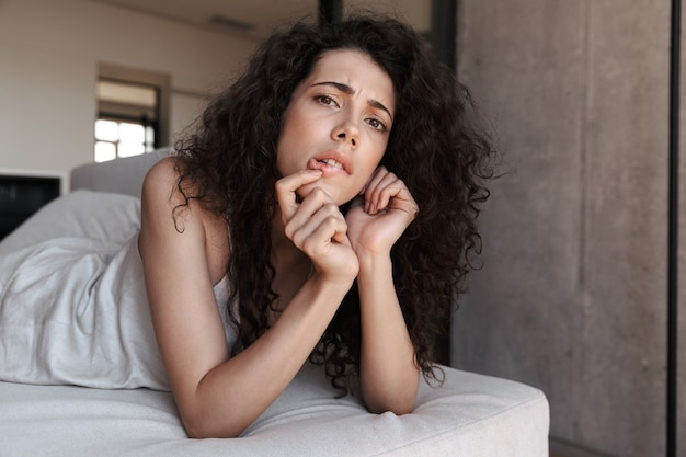 Closeup photo of uptight thoughtful woman with long curly hair wearing silk leisure clothing lying in hotel bed or sofa, and biting lips while propping up her head with hand