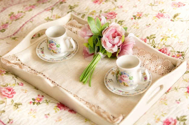 Closeup photo of vintage tray with flowers and teacups lying on bed